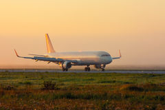 Plane on the taxiway. In the early foggy morning Stock Photo
