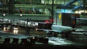 Plane at terminal gate, night view, Munich. Lufthansa jet in Munich Airport, night view. Plane waiting passenger onboarding stock video