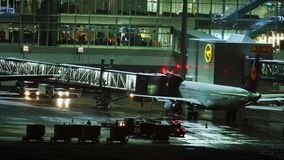 Plane at terminal gate, night view, Munich. South African jet in Munich Airport, night view. Plane waiting passengers onboard stock footage