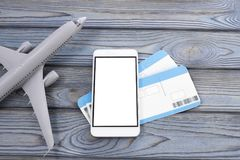 Plane, tickets, smartphone with a white screen on a wooden background. Journey. tourism. air transportation stock images