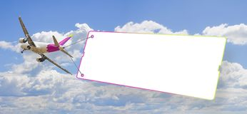 Plane towing a blank signboard against a blue sky - concept image with space for text stock images