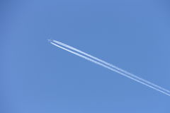 Plane with trail. Plane in blue sky with trail Stock Photos