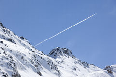 Plane trail over snowy mountain Stock Photography