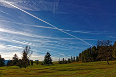 Plane trails over Allgau Alps landscape. Air traffic: Many plane trails in the sky over the Allgäu Alps landscape, Germany, with its deep colors in late fall Royalty Free Stock Photography