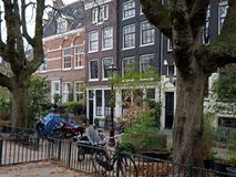 Plane-trees in the playground and old house-fronts in Amsterdam city. Plane-trees in an urban playground for children and 17th century old house-fronts in stock photo