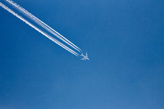 Plane with vapor trails in a blue sky Stock Photography