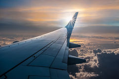Plane View. A view out of the window of an Airplane. The sun is just behind the wing and flying above the clouds Stock Photos