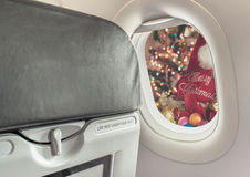 Plane window and Christmas ornaments . Image of plane window and Christmas ornaments on wood background Royalty Free Stock Photography