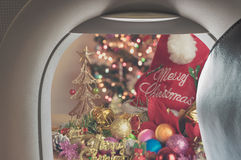 Plane window and Christmas ornaments . Image of plane window and Christmas ornaments on wood background Royalty Free Stock Photos