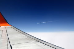 Plane wing. The view of the plane wing on the blue and white sky background Royalty Free Stock Images