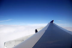 Plane wing on a blue day Stock Photos