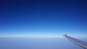 Plane wing with blue horizontal skyline with no cloud Royalty Free Stock Images