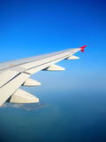 Plane wing in a blue sky above tropical island Stock Photography