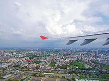 Plane wing and blue sky with city of Bangkok underneath. Flying plane& x27;s wing and blue sky with city of Bangkok underneath Stock Photography