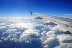 Plane wing flying above the clouds Stock Images