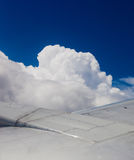 Plane wing, ground, clouds and sky Stock Photos