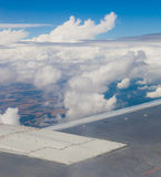 Plane wing, ground, clouds and sky Royalty Free Stock Images