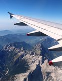 Plane wing over Alps, Summer with mountains below Stock Photos
