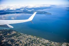 Plane wing over Anchorage. ANCHORAGE, AK -AUG 31, 2017- Airplanes are taking off from Ted Stevens Anchorage International Airport ANC in Alaska royalty free stock photography