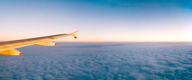 Plane wing over clouds. Right plane wing over blue clouds with copy space Stock Photos
