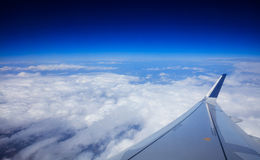 Plane wing over clouds on a blue sky background Royalty Free Stock Image