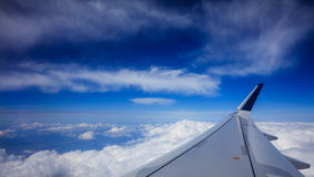 Plane wing over clouds on a blue sky background Stock Photo