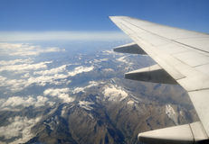 Plane wing over mountains. Airplane wing flying over mountains and clouds with a blue sky Royalty Free Stock Photo