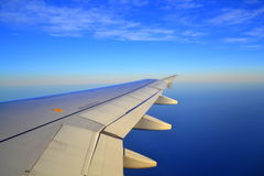Plane wing on sky. Wing of plane on bright blue sky and Mediterranean sea horizon Royalty Free Stock Photography