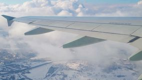 Plane wing through window with sky and city behind. Aircraft turn at flight.  stock footage