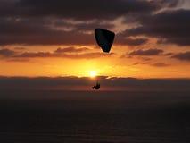 Planeador de caída en puesta del sol, lejos Imágenes de archivo libres de regalías