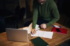 Planeamiento del hombre de negocios que trabaja en horas extras en espacio coworking usando la tecnología y el wifi modernos, vis Foto de archivo