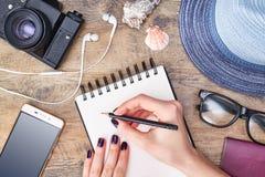 Planeamiento del viaje La mujer escribe en el cuaderno en fondo de madera imagenes de archivo