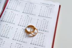 Planeando casarse en 2018 Calendario de 2018 y dos anillos de bodas y en el fondo blanco Fotos de archivo