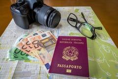 Planeando pasaportes italianos y brasileños de un viaje - en ciudad trace con el dinero, la cámara y los vidrios de las cuentas d fotografía de archivo