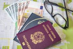 Planeando un pasaporte italiano y brasileño del viaje - en mapa de la ciudad con euro carga en cuenta el dinero y los vidrios imagen de archivo libre de regalías