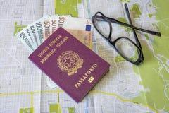 Planeando un viaje - el pasaporte italiano en mapa de la ciudad con euro carga en cuenta el dinero y los vidrios fotografía de archivo libre de regalías