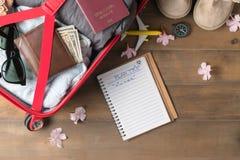 Planee el viaje en el cuaderno y prepare los accesorios y los artículos del viaje Imagen de archivo libre de regalías