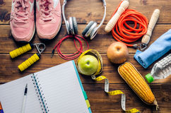 Planeie o conceito da aptidão com equipamento do exercício e alimento saudável no fundo de madeira imagem de stock royalty free