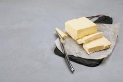 Planen Sie Brett mit geschmackvoller frischer Butter und Messer Lizenzfreies Stockbild