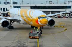 Planen Sie das Fluglinie NokScoot-Jet-Flugzeug, das an Flughafen Thailand Bangkoks Suvarnabumi geschleppt wird Lizenzfreie Stockfotografie