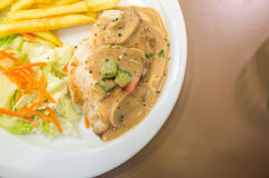 Planen Sie Hühnersteak mit Pilzsoße und Pommes-Frites Lizenzfreies Stockbild