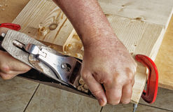 Planer carpenter who takes a chamfer boards. Chamfering the board with the help of the planer Stock Images