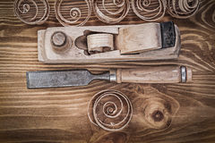 Planer chisels curled shavings on vintage wooden board construct Stock Images