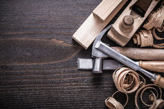 Planer claw hammer firmer chisels wooden bricks. And curled shavings on vintage wood board construction concept Royalty Free Stock Photo