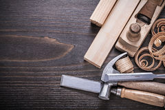 Planer claw hammer metal chisels wooden studs and. Curled shavings on vintage wood board construction concept Royalty Free Stock Photo