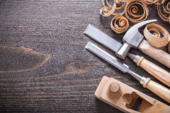 Planer claw hammer metal firmer chisels and wooden. Curled shavings on vintage wood board construction concept Stock Photos