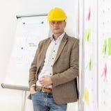 Planer, der an einer Wand mit Planungsdetails sich lehnt lizenzfreie stockbilder