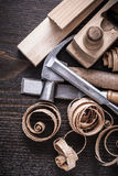 Planer hammer chisels wooden studs and curled. Shavings on vintage wood board construction concept Stock Images