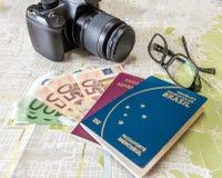 Planera brasilianska och italienska pass för en tur - på stadsöversikt med euro fakturerar pengar, kameran och exponeringsglas arkivfoton