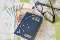 Planera en tur - det brasilianska passet på stadsöversikt med euro fakturerar pengar och exponeringsglas Royaltyfri Foto